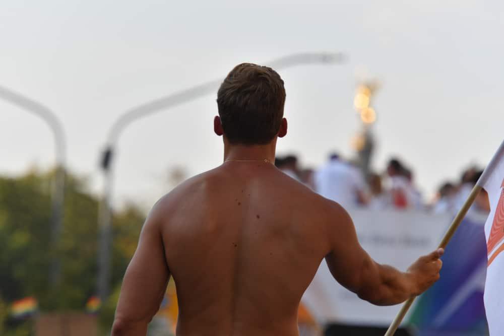 Ryggen af en muskuløs mand i bar overkrop til Christopher Street Day i Berlin.