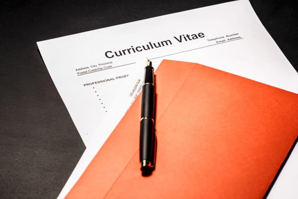 Jobansøger sidder ved bord overfor potentiel arbejdsgiver. Arbejdsgiver kigger på CV.