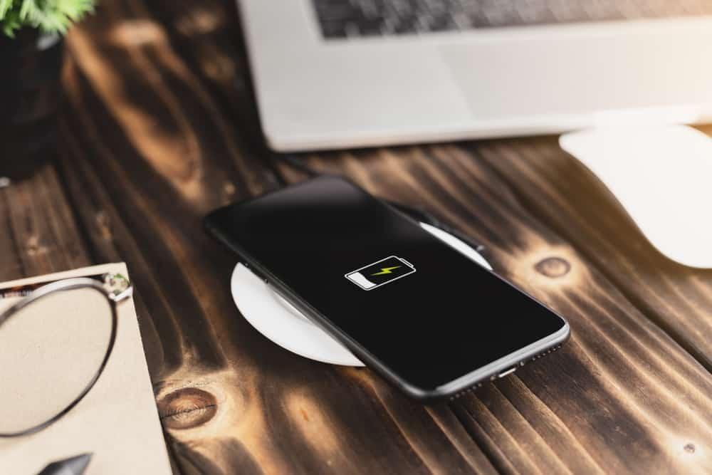 Mobiltelefon på bord, som bliver opladet af trådløs enhed.