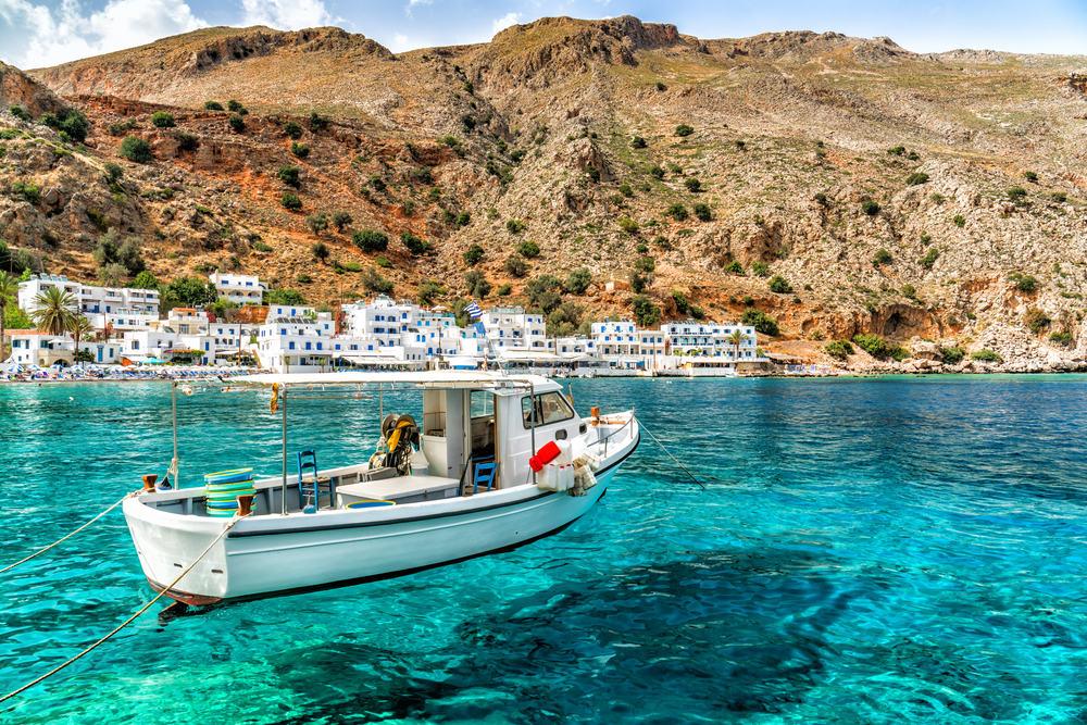 Fiskerbåd på Kreta med bjerge i baggrunden.