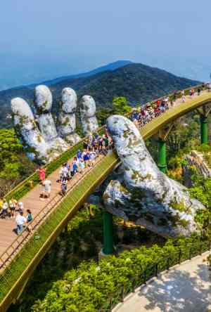 Bro der holdes oppe ad hænder. Turister på broen.