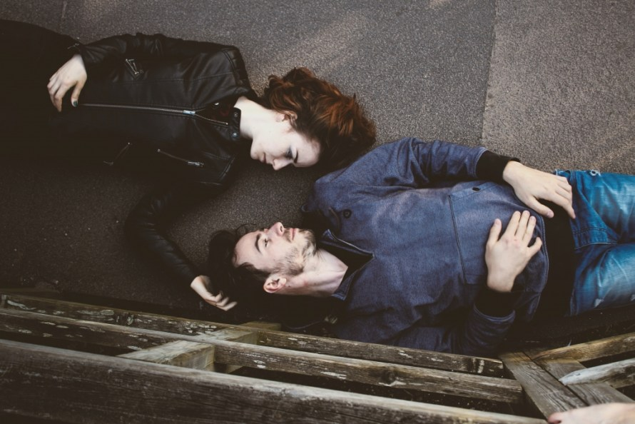 Dating tips for women: Woman and man laying on the ground gazing at each other.