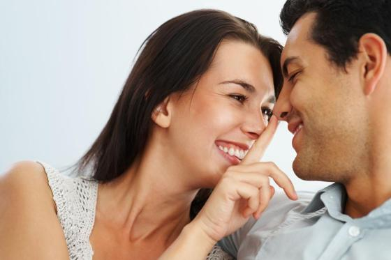 woman flirting before sex, with man. Woman has her finger on the man's nose as he smiles.
