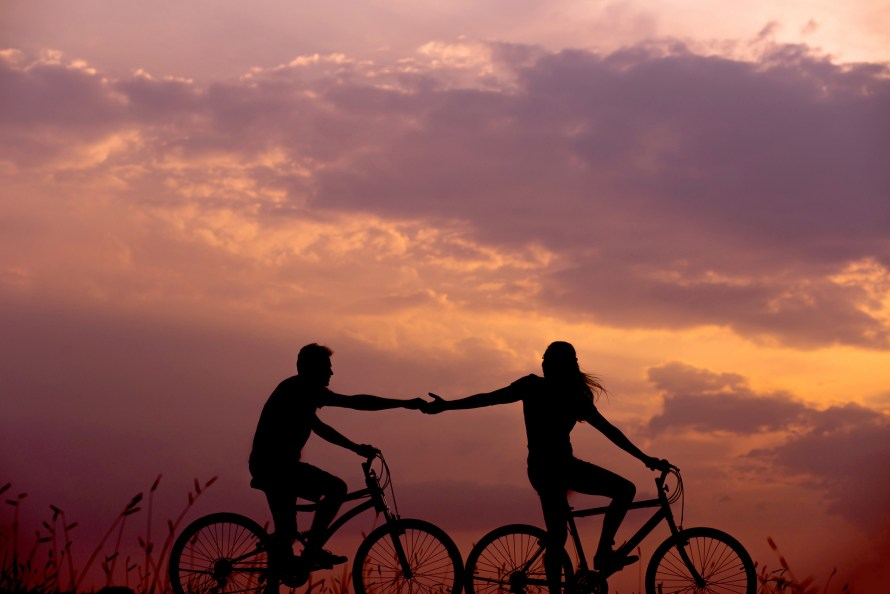 Woman and man riding bicycles together