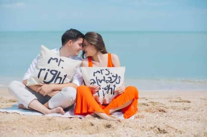 photo man and woman wearing cloths sitting on brown sand near seashore