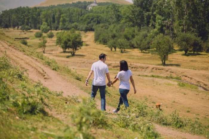 man and woman walking in the countryside