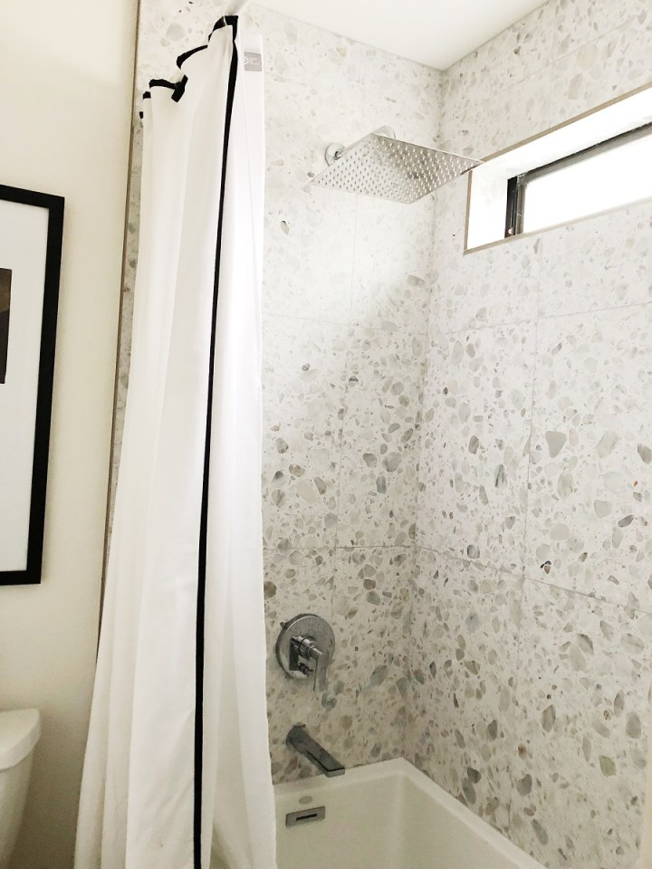 Ann Sacks Terrazzo tile floor to ceiling bath tub and Shower combo. Black Accents.