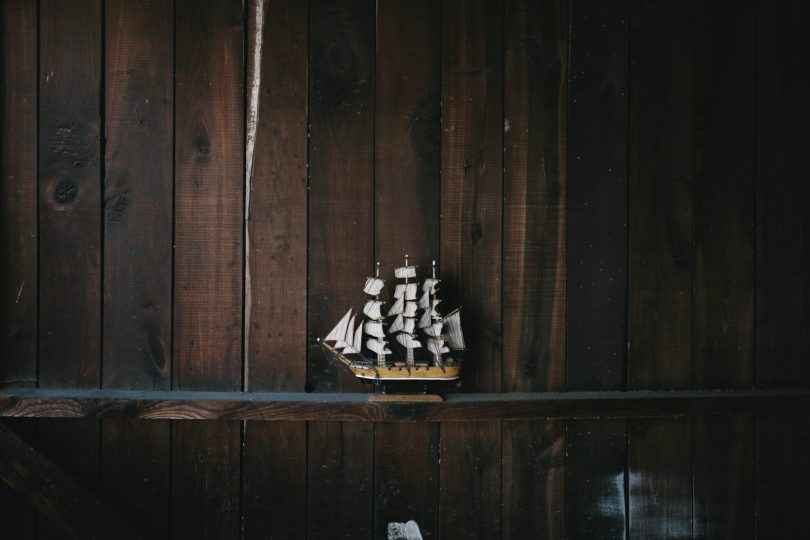 black, brown, and white galleon ship scale model on brown wooden shelf because someone took the time to build it