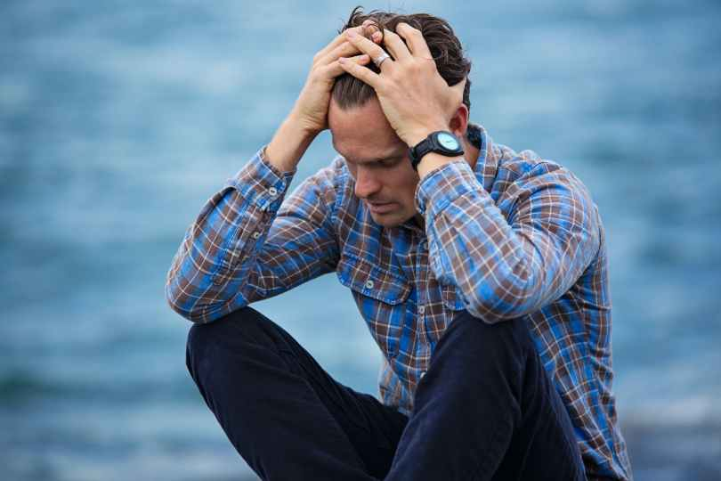 man in blue and brown plaid dress shirt touching his hair in stressed out manor