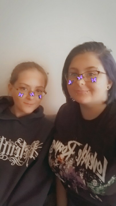 Ember sitting next to her sister Sheaylam, both smiling with purple butterflies around their face from a filter.