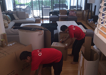 Two movers packing moving boxes