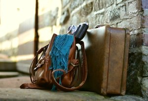 A suitcase and a bag leaning against a wall.
