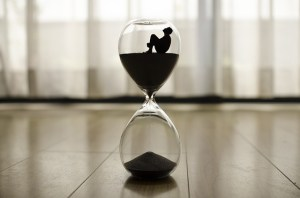 An hour glass with a figure of a man inside, trying to choose international movers on time.