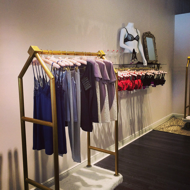Brass rolling clothes racks, from the Peabody Hotel in Orlando, are part of the new store's theme