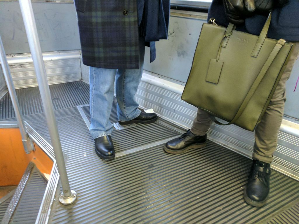 Care Label trousers, Prada bag, and Bottega Veneta boots on the tram in Milan