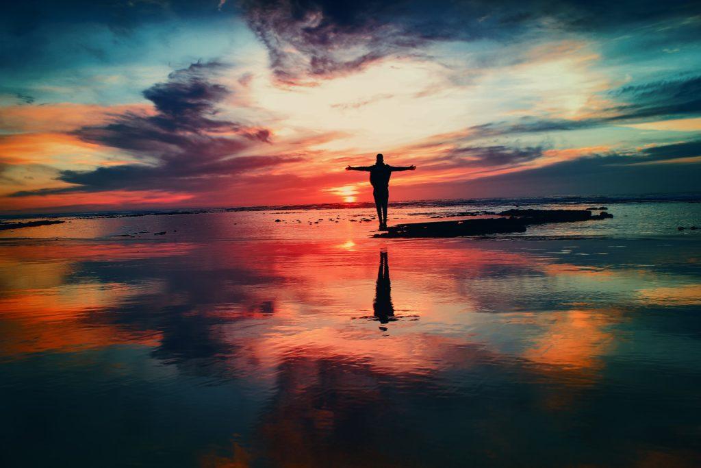 silhueta pessoa com braços abertos a beira mar