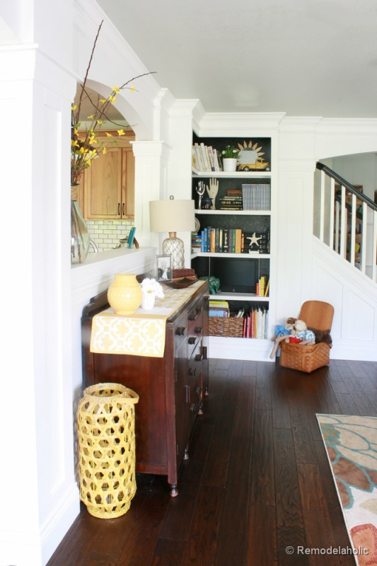 Living Room Remodel with yellow accents wood floors and built-in bookcases and columns with arches-22
