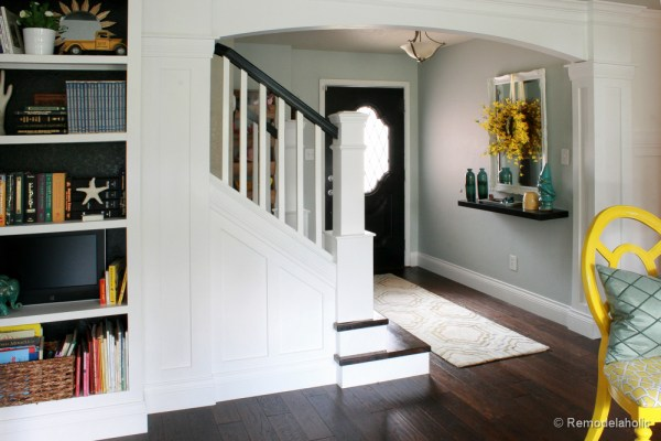 Living Room Remodel with yellow accents wood floors and built-in bookcases and columns with arches-33