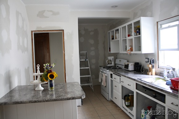 white kitchen remodel in progress, after thrifted cabinet installation