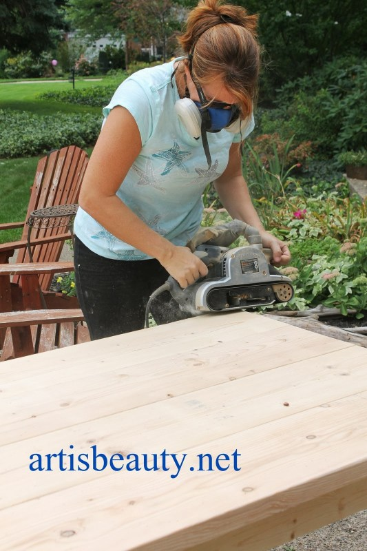belt sander to round down and age the corners of the diy farmhouse table, featured on Remodelaholic.com
