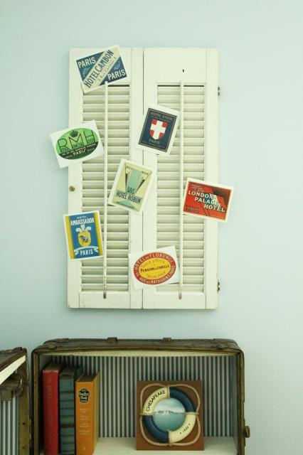 travel postcard shutter display above antique trunk turned bookshelf, featured on Remodelaholic.com