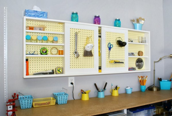 DIY tutorial - pegboard tool cabinet with sliding doors, featured on Remodelaholic.com