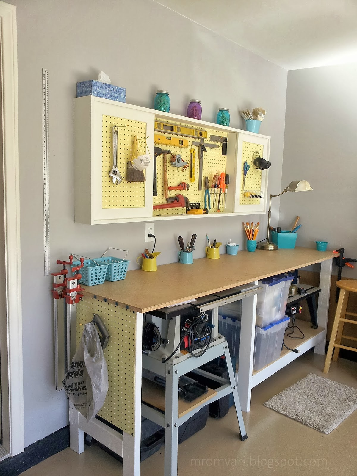 DIY tutorial to build a workbench and pegboard tool cabinet with sliding doors, featured on Remodelaholic.com