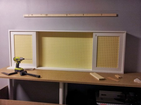 assembled pegboard tool cabinet with sliding doors, featured on Remodelaholic.com