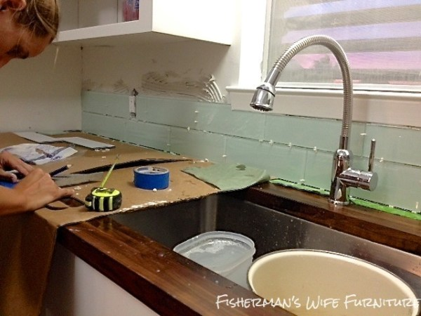 installing glass subway tile backsplash in small kitchen remodel, Fisherman's Wife Furniture featured on Remodelaholic.com
