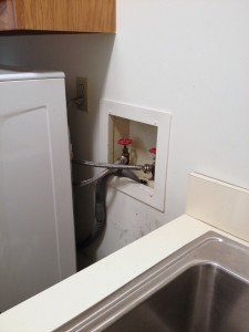 hide plumbing access in laundry room, featured on Remodelaholic