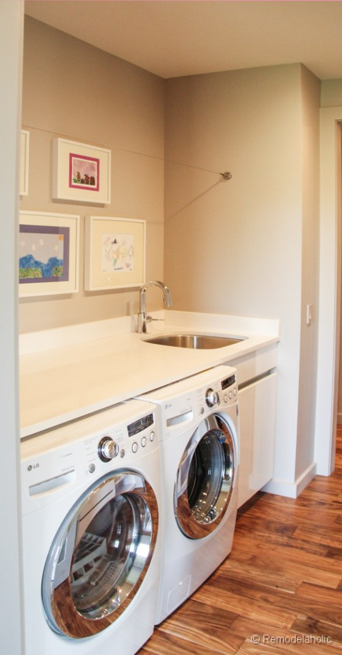 Simple laundry room with clothes line. Fabulous Laundry room design ideas from @Remodelaholic
