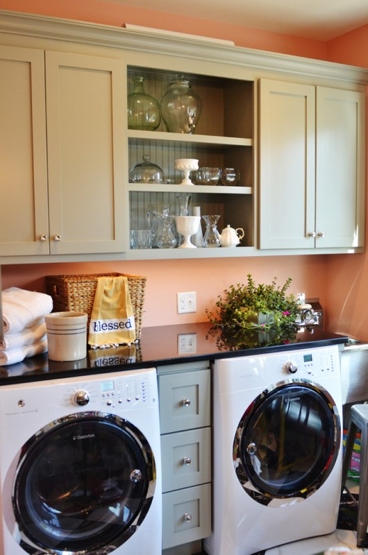 Simple laundry room with colored cabinets and storage featured on remodelaholic.com