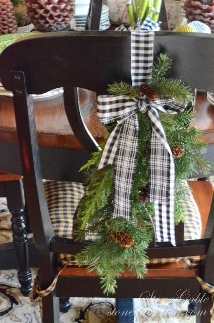 use pine garland and fabric to decorate dining chairs for holiday - Stonegable Blog via @Remodelaholic