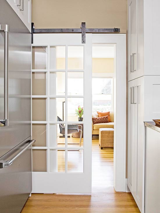 Beautiful Doors - white french door with glass panes on barn style hardware via BHG