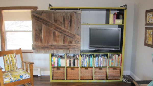 add a pipe rail to a shelving unit for a sliding rustic door to hide the tv (via Ikea Hackers)