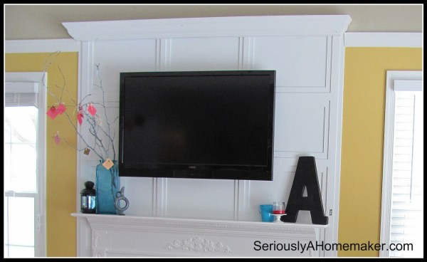 how to hide tv cords in trimwork above the mantel (via Sawdust Girl)