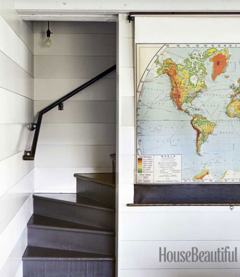 use a pull down map or shade to hide the television (House Beautiful)