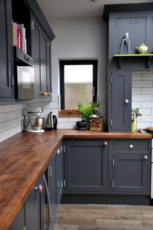 black kitchen cabinets with colorful knobs and wood countertops