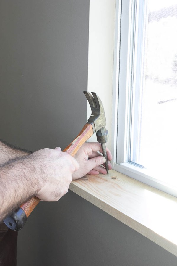 Nailing on window trim tutorial featured on Remodelaholic.com