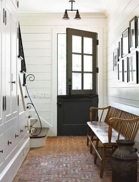 A black Dutch door and exposed brick in the entryway. Add this to my dream home list! and look at all that storage under the stairs!