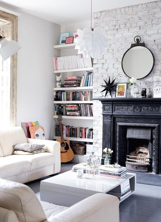 Gorgeous black fireplace on a white wall with floating shelves