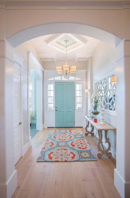 Turquoise and orange accents in the entryway, plus the mirror and table are AMAZING | 100+ Beautiful Mudrooms and Entryways at Remodelaholic.com