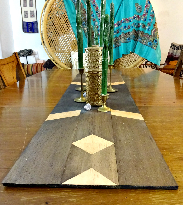 eclectic dining room display. wooden geometric table runner with brass candlesticks and quirky candles