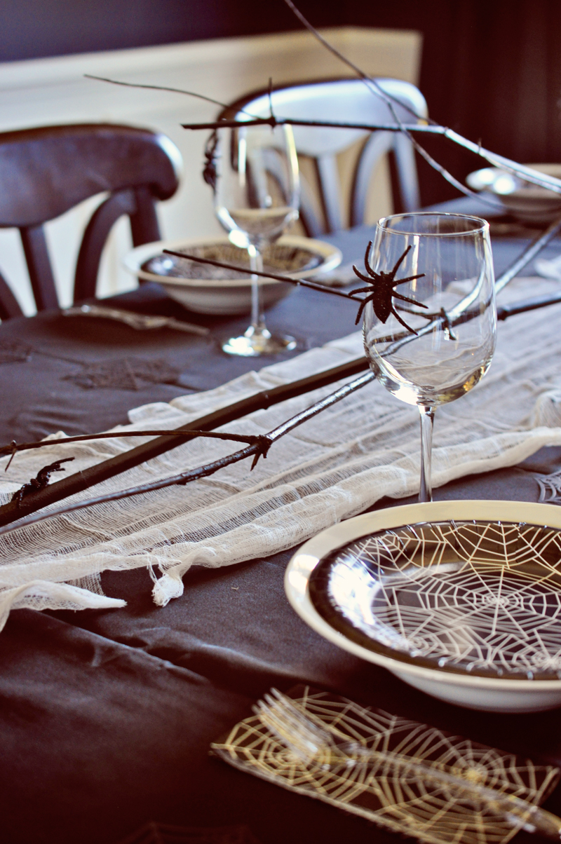 Easy Halloween table setting, using spray painted branches and cheesecloth as a runner | Simple Halloween Decor Ideas and Tutorials at Remodelaholic.com