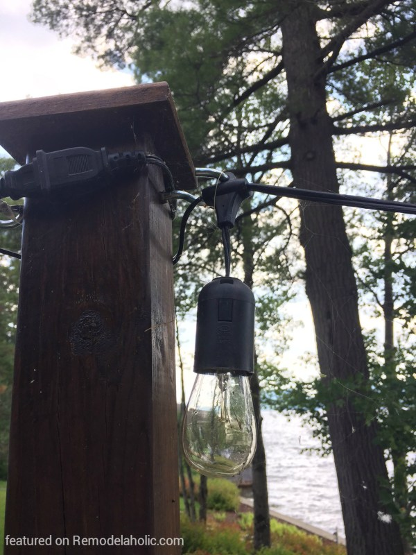 easy DIY method how to hang string lights on posts around a fire pit, featured on @Remodelaholic wm