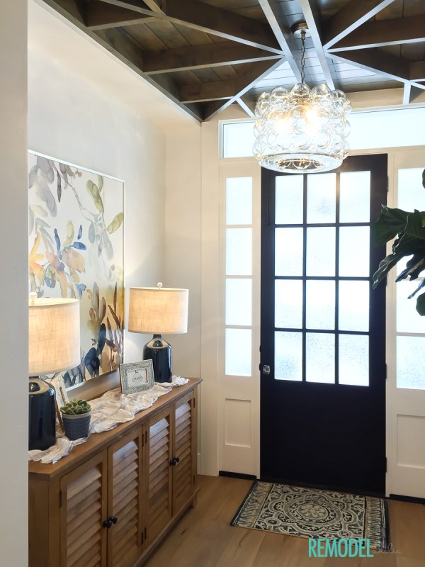 Learn how to get the look of this transitional entryway with black interior door, white trim work, wood ceiling details, bubble chandelier, navy blue lamps, wood shutter console table and fiddle leaf fig tree.