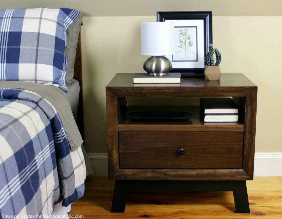 This chunky wood nightstand is made from solid wood and features angled mid-century style legs, an open shelf, and a sliding drawer for storage. Free building plan and tutorial.