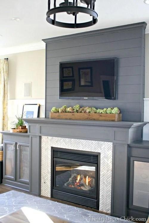 Ideas for Decorating Around a TV Over the Fireplace Mantel, gray shiplap mantel surround via Thrift Decor Chick