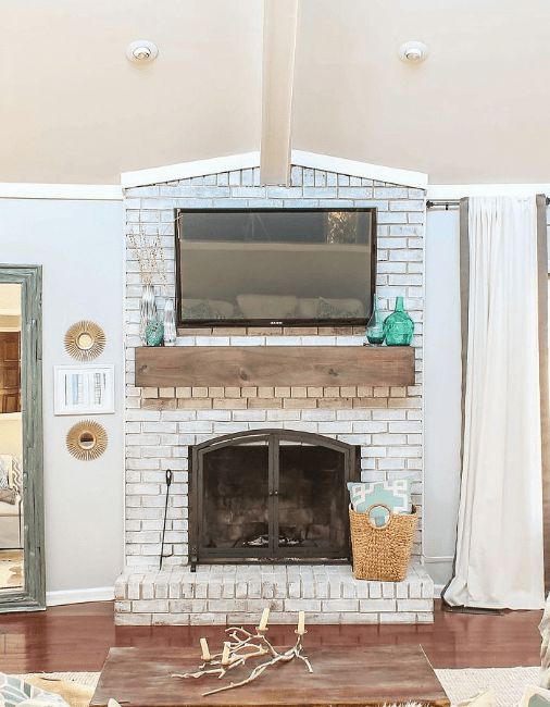 Ideas for Decorating Around a TV Over the Fireplace Mantel, white painted brick fireplace with wood mantel via Designing Vibes