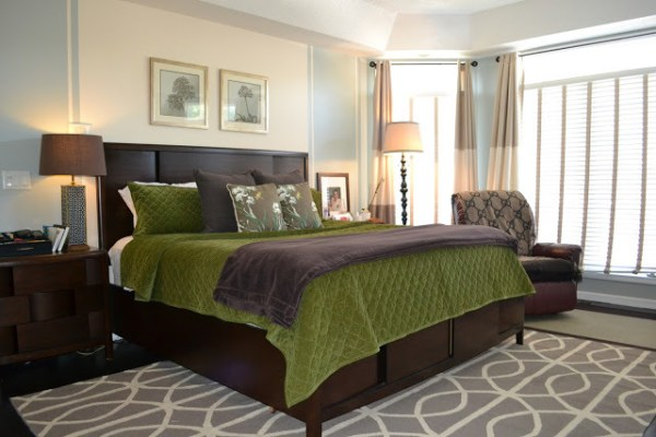 Bedroom With Large Window And Dark Wood Headboard And Frame And Nighstands With Green And Brown Bedding And Dark Leather Rocker Recliner